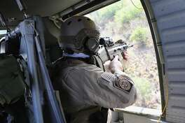 A U.S. Customs and Border Protection (CBP) agent aims his weapon from a Black Hawk helicopter while pursuing a truck with suspected undocumented immigrants on February 21, 2018 in McAllen, Texas. Air interdiction agents from U.S. Air and Marine Operations, U.S. Border Patrol agents and Texas state troopers conducted the high-speed chase, after a pickup failed to yield and then raced to the Mexican border. The vehicle crashed into a tree on the Texas side of the Rio Grande, and the three occupants evaded arrest before swimming into Mexico.  (Photo by John Moore/Getty Images)