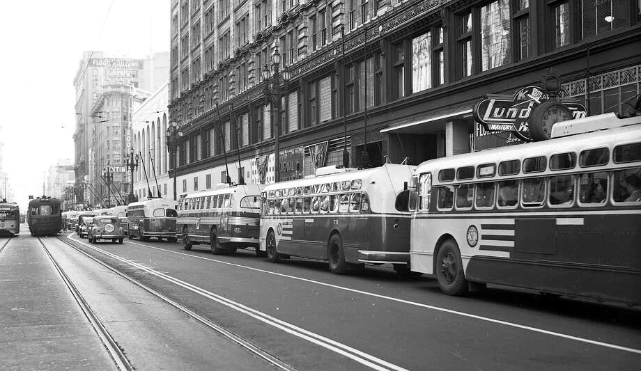 "A row of new Municipal Railway electric ""trackless trolley"" buses wait for service on Market Street in San Francisco on July 5, 1949. Photo: Bob Campbell, The Chronicle"