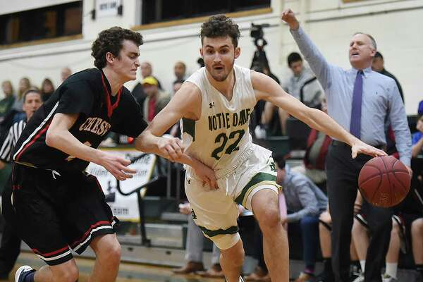 Notre Dame-West Haven's Connor Raines, right, drives to the paint as Cheshire's James Pettit defends on Thursday in West Haven.