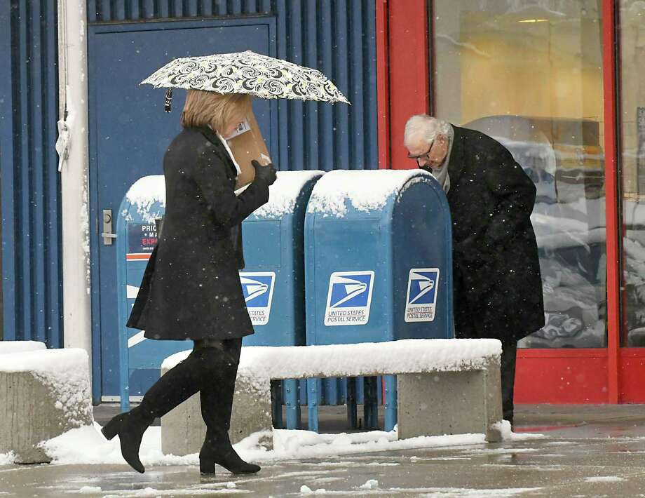 A women uses an umbrella as she carries a package into the Post Office at Stuyvesant Plaza during a snow storm on Thursday, Feb. 22, 2018, in Guilderland, N.Y. (Lori Van Buren/Times Union) Photo: Lori Van Buren / 20043006A