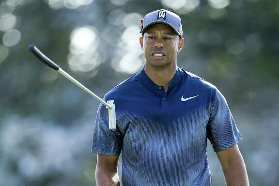 Tiger Woods appeared frustrated as he flips his club on the 15th green at the Honda Classic. He parred the hole and shot even-par 70 and is four strokes behind.
