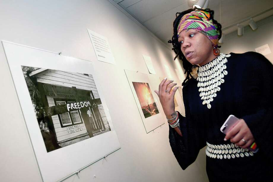 """Orisha Ala, co-founder of New Haven Black Lives Matter, looks at a photograph titled """"Freedom House"""" Thursday at the Margaret L. MacDonough Art Gallery during Albertus Magnus College's celebration of Black History Month. Photo: Catherine Avalone / Hearst Connecticut Media / New Haven Register"""