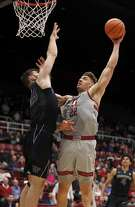 Stanford forward Reid Travis (22) takes a shot over Washington forward Sam Timmins (33) during the first half of an NCAA college basketball game Thursday, Feb. 22, 2018, in Stanford, Calif. (AP Photo/Tony Avelar)