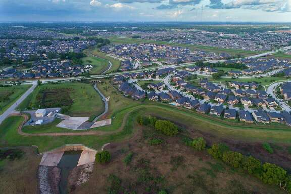 A levee protects portions of the Riverstone neighborhood where Steep Bank Creek runs toward the Brazos River.