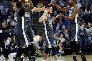 Golden State Warriors' Draymond Green, JaVale McGee, Stephen Curry and Kevin Durant celebrate a 1st quarter basket against Los Angeles Clippers during NBA game at Oracle Arena in Oakland, Calif., on Thursday, February 22, 2018.