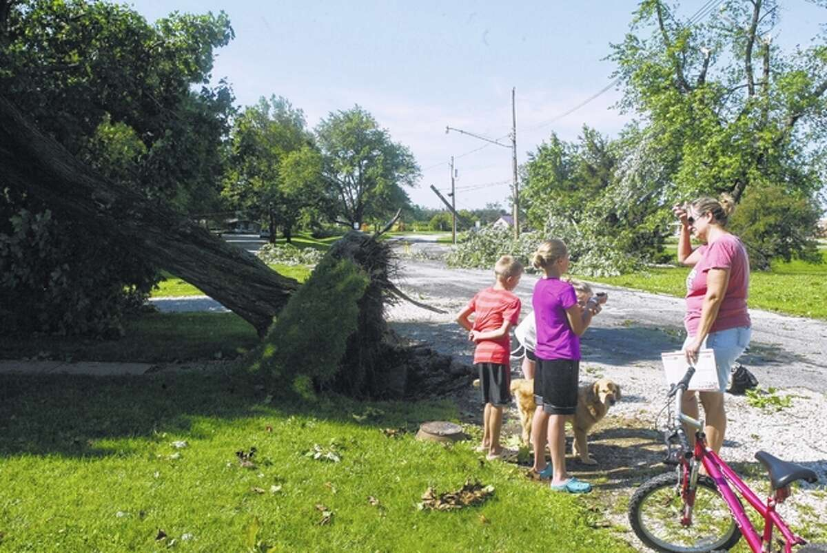 Contina Savage (right) of Winchester talks to a group of children who were riding their bikes around the city Tuesday morning, surveying damage from a storm that swept through the area Monday night, causing damage and power outages. Savage's home was damaged by an large uprooted tree that fell onto the home's front porch roof. Broken trees and power lines along Savage's street can be seen in the background.