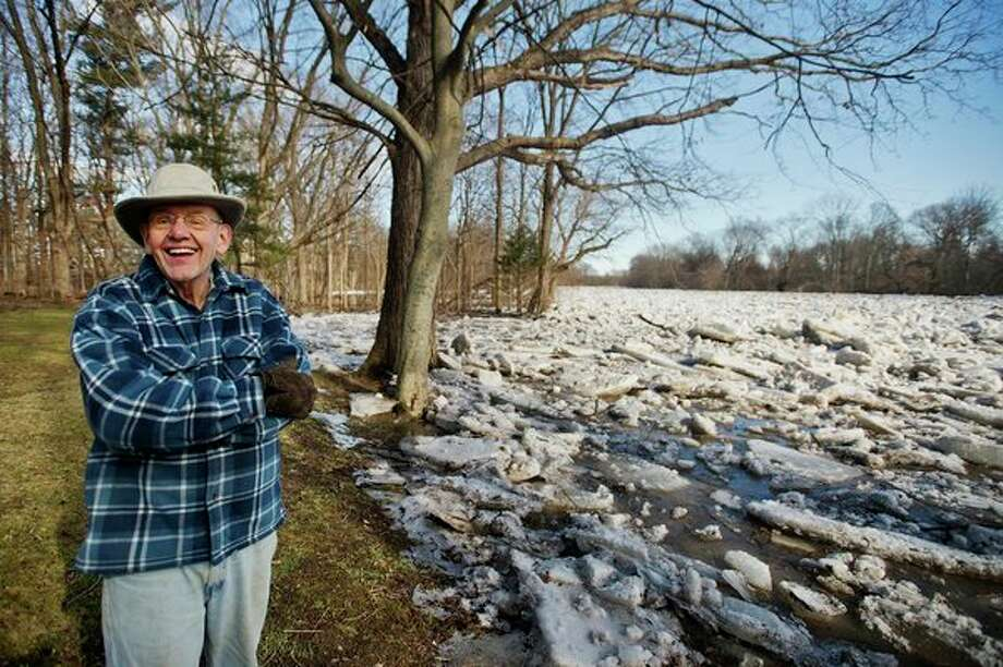 Midland resident Gene Anderson poses for a portrait in his backyard, as large sheets and chunks of ice are piled up in the Chippewa River behind him on Thursday afternoon. Flooding caused the ice to slowly inch farther onto Anderson's property, though it never reached his home. (Katy Kildee/kkildee@mdn.net)
