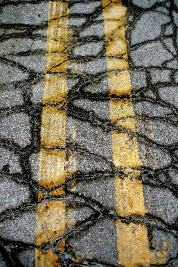 Cracks in the asphalt crisscross between the double-yellow line on Ashman Street between the U.S. 10 overpass and Rockwell Road. (Daily News file photo) / Midland Daily News