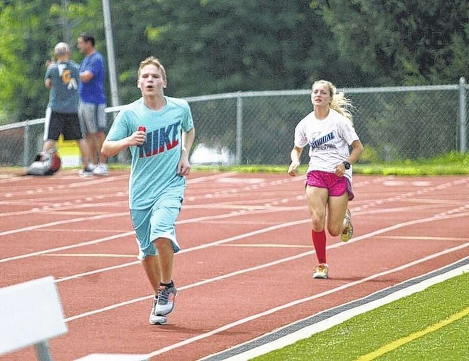 Two young runners run the track around Illinois College's England Stadium during the Fellowship of Christian Athletes Illinois State Sports Camp held this week at IC. The camp concluded Thursday with a short session.