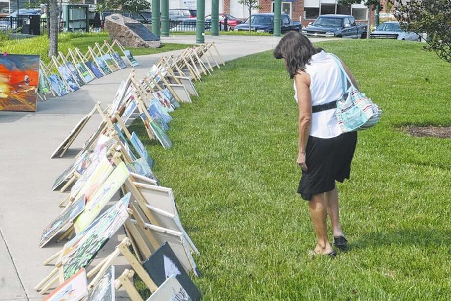 Sharon Bonjean looks at paintings by artist Ed Owen he had displayed in downtown Jacksonville on Wednesday. Photo: Nick Draper | Journal-Courier