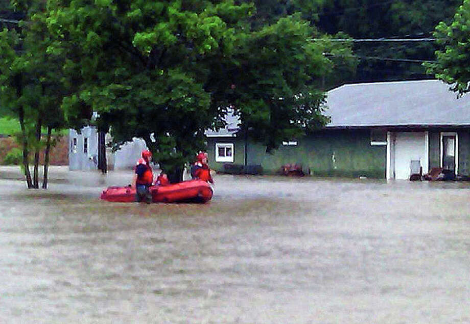 Samantha McDaniel-Ogletree | Journal Courier Rescuer workers make their way to a house in which several people were stranded following flooding in Hillview caused by levee breaks along Hurricane Creek.