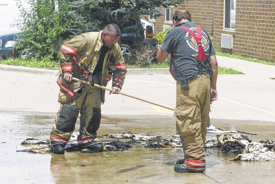 A South Jacksonville firefighter sweeps together a pile of burnt towels after a small dryer fire at the Baymont Inn and Suites around 1:50 p.m. Monday. The fire was quickly contained, although the sprinklers were set off and soaked the area. Aside from the damage to the dryer and the burned towels, no other damage was reported.