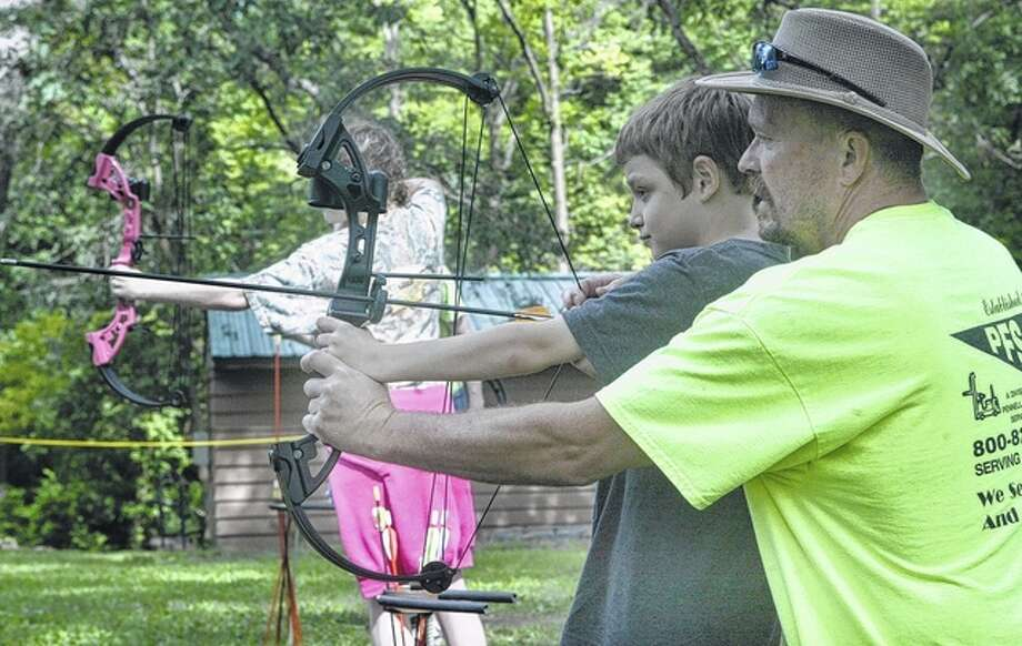Camp Courage co-director John Hunter helps a young camper on the archery range. Photo: Greg Olson | Journal-Courier