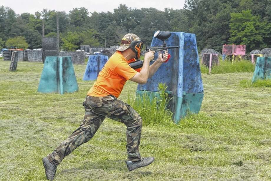 Paintball to Go owner Joe Schnelten runs to take cover during a small paintball match. Photo: Nick Draper | Journal-Courier