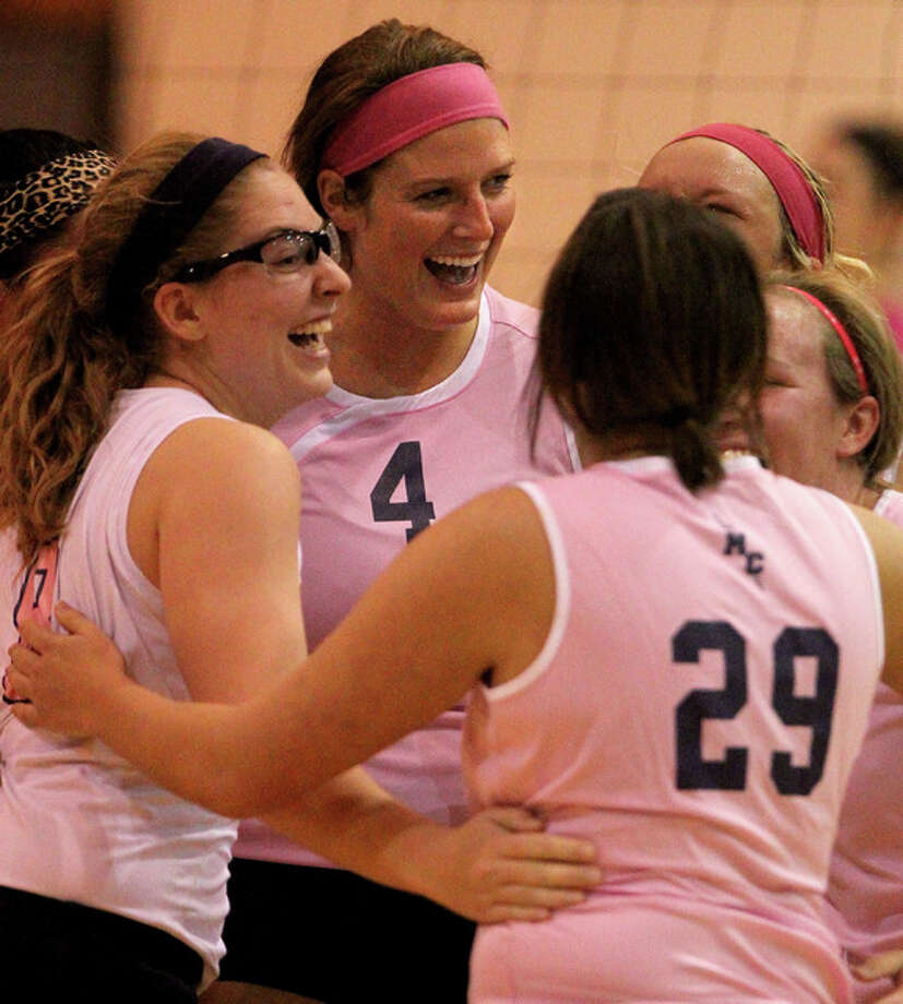 MacMurray College volleyball player Breanne Pelker (4) celebrates with teammates after a win last season. On Wednesday the Highlanders won their third straight AVCA Team Academic Award. Photo: Dennis Mathes   Journal-Courier File