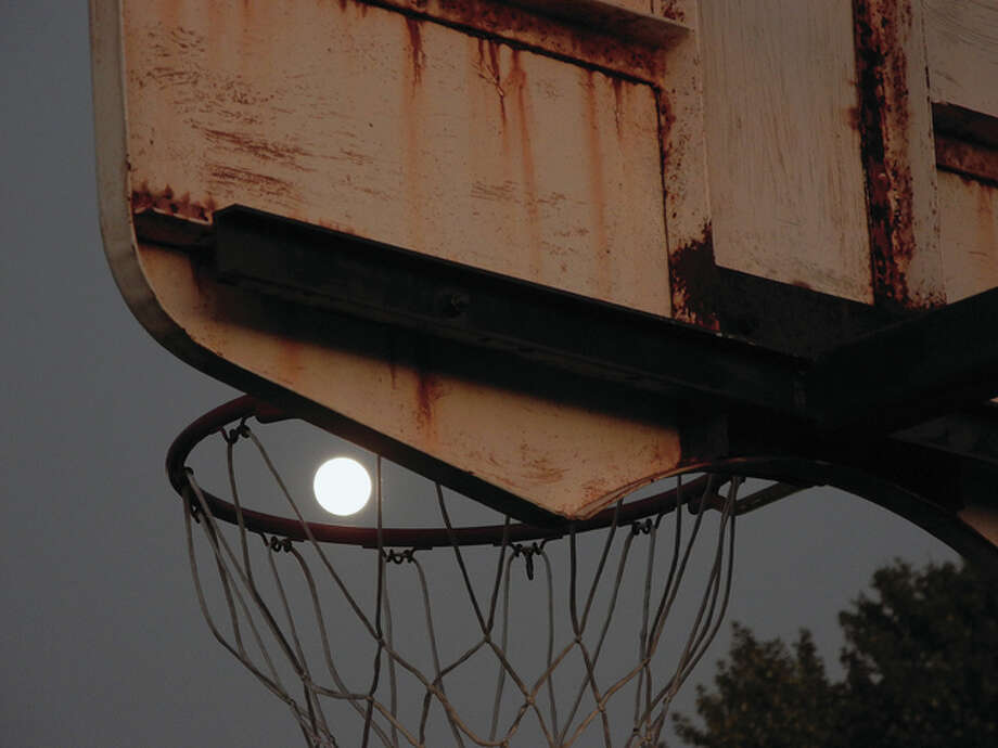 The moon peeks through a basketball hoop on the playground at Eisenhower Elementary School. Photo: David Blanchette | Reader Photo