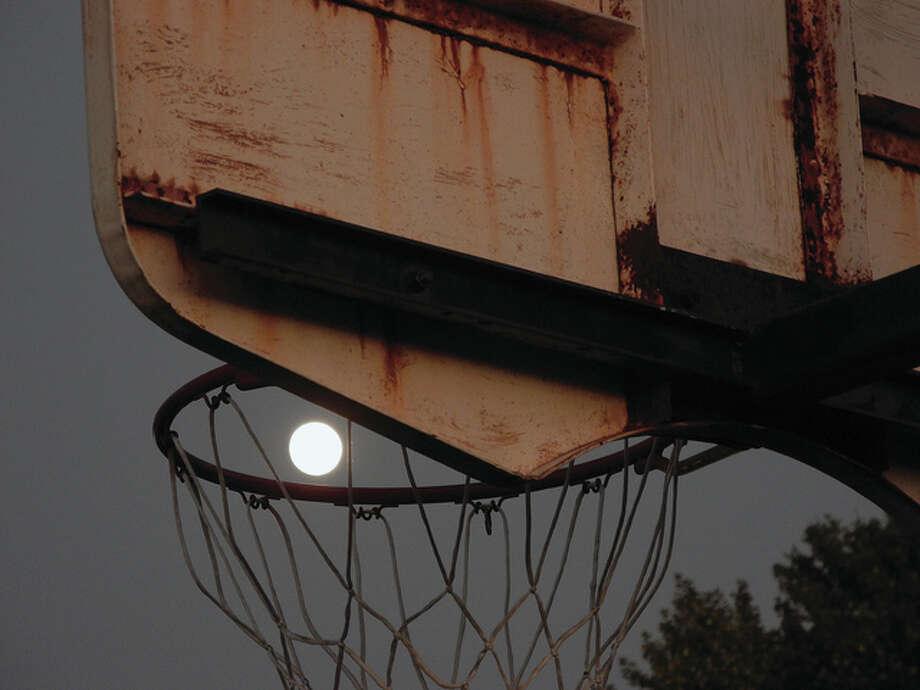The moon peeks through a basketball hoop on the playground at Eisenhower Elementary School. Photo: David Blanchette | Reader Photo