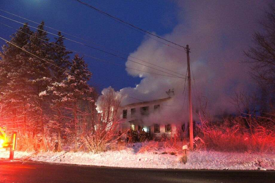 A farm house burns in Schodack on Friday morning. The blaze on Route 150 dew dozens of firefighters who worked frantically to save the building. Photo: Martin Miller / Special To The Times Union