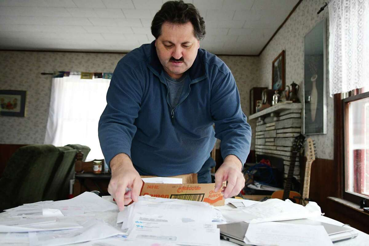 Joseph Lestingi sorts through paperwork on Tuesday, Jan. 30, 2018, at his home in Clemons, N.Y.
