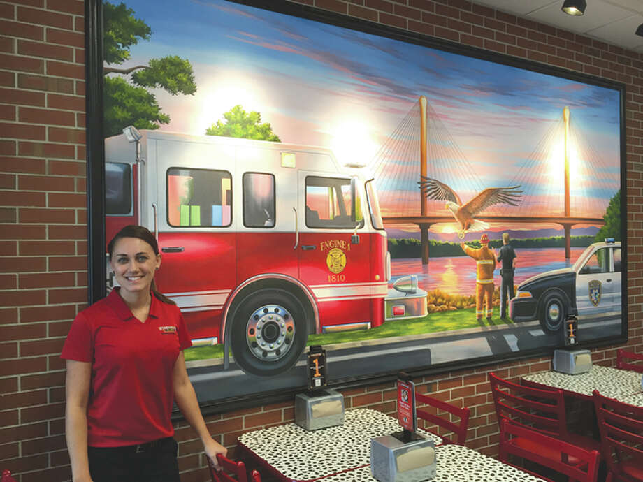 Firehouse Subs' Alton location owner, Hannah Mazanek Lukowski, stands next to the one-of-a-kind mural painted for the franchise. The restaurant opened Thursday at 317 J Homer Adams Parkway.