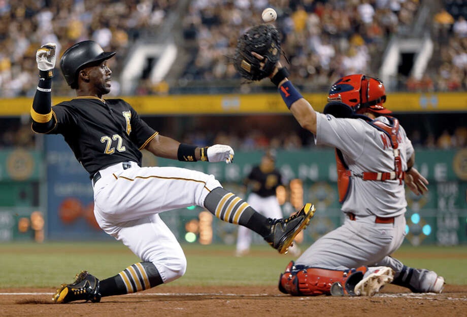 The Pirates' Andrew McCutchen (left) scores a run as the ball gets away from Cardinals catcher Yadier Molina during the eighth inning Saturday night in Pittsburgh. Photo: Associated Press