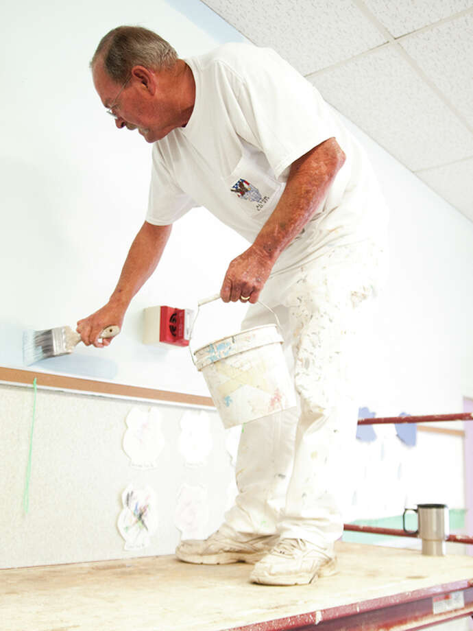 Cy Austin volunteered his time to help paint one of the rooms on Saturday morning at the Alton Day Care Center-Mckinley Site.
