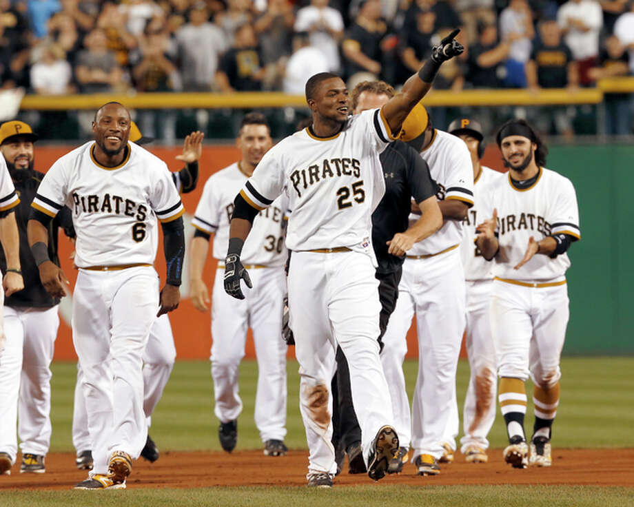 The Pirates' Gregory Polanco (25) points to the stands as he leaves the field while celebrating with teammates after driving in the winning run to defeat the Cardinals in the 10 inning Sunday night in Pittsburgh. Photo: Associated Press