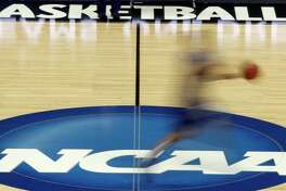 FILE - In this March 14, 2012, file photo made with a long exposure, a player runs across the NCAA logo at midcourt during practice in Pittsburgh before an NCAA tournament college basketball game. The NCAA last year cut in half the penalty for athletes who fail screenings for substances like marijuana, and its chief medical officer is pushing for college sports' governing body to get out of the business of testing for recreational drugs altogether. The AP found that some of the nation's biggest universities, from Oregon to Auburn, have already eased their punishments as society's views on marijuana use have changed. (AP Photo/Keith Srakocic)