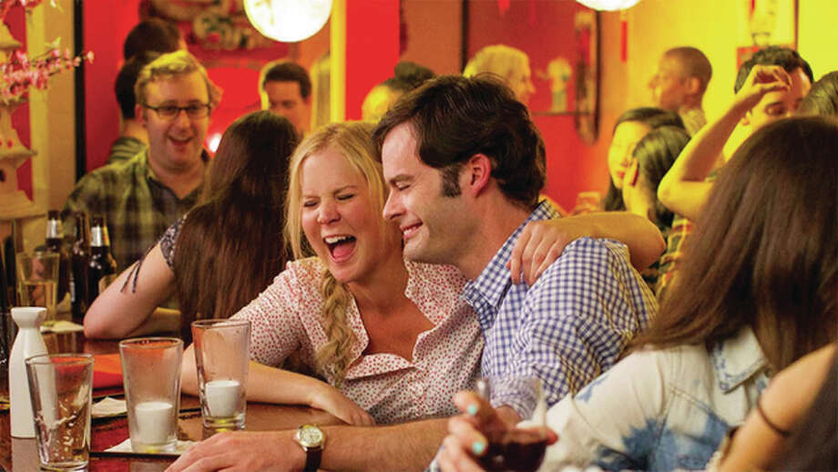 """Trainwreck,"" starring and written by Amy Schumer, left, it chronicles the promiscuous misadventures of commitment-phobic magazine writer. When her boss (Tilda Swinton) assigns her to write about a sports surgeon, Dr. Aaron Conners, (Bill Hader, right) something happens to the movie's main character, Amy, who for the first time falls in love. Photo: Image Courtesy Of Universal 
