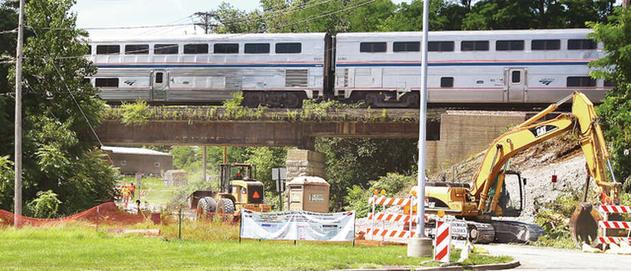An Amtrak train speeds over the wooden tied railroad viaduct over Seminary Street in Alton just north of Claire Street as workers in heavy equipment clear trees and brush to make way for a new viaduct. The railroad ties on the old viaduct are rotting and in poor condition. The new viaduct will be supported by pillars farther apart making the roadway wider and safer underneath.