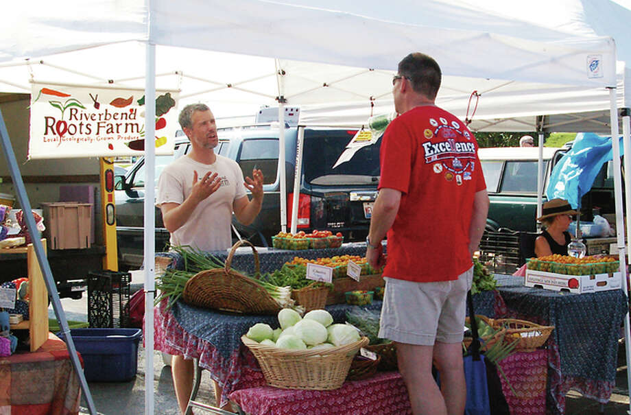 Kris Larson of Riverbend Roots Farm talks to a customer about his organic, sustainably grown produce at the Alton Farmers and Artisans Market Saturday.