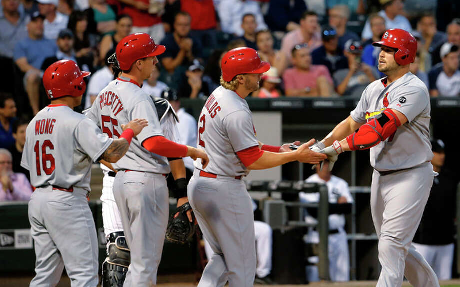 The Cardinals' Matt Holliday (right) is greeted at home by (from left) Kolten Wong, Steven Piscotty and Mark Reynolds after they scored on Holiday's grand slam during the fourth inning Tuesday night in Chicago.