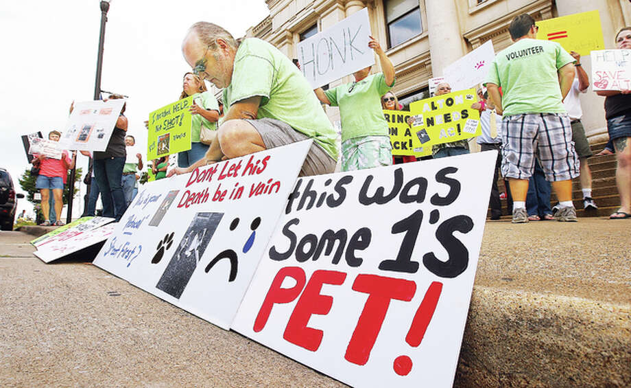 For the second time this month, protestors opposed the possibility of losing the Alton animal control officer position to budget cuts, gathered at Alton City Hall to protest. About 80 people with homemade signs showed up, apparently spurred by the shooting of a dog this week by Alton Police, who are handling most animal complaints right now.