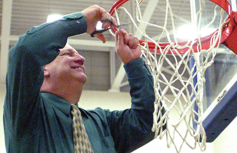 Carrollton coach Jeff Krumwiede cuts the net after the Hawks' Class 1A regional title victory over the host Spartans on Feb. 27 in White Hall. Carrollton finished 27-5 and Krumwiede is 2015 Telegraph Small-Schools Boys Basketball Coach of the Year. Photo: Dennis Mathes, Journal-Courier | For The Telegraph