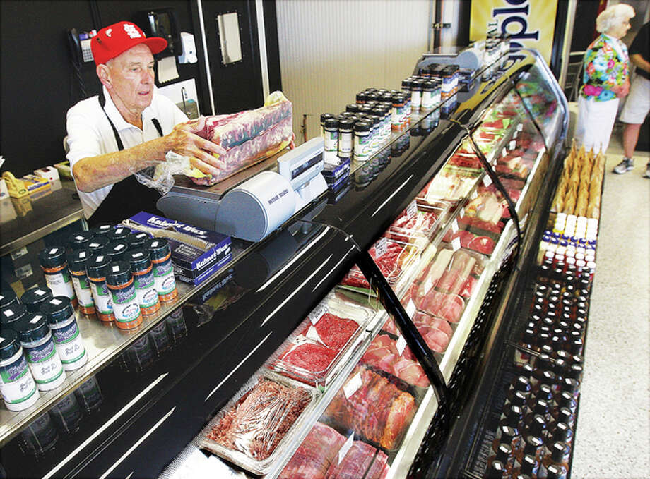 A worker at Hansen Meat Co. weighs meat on a scale during the store's grand opening Friday. Photo: John Badman | The Telegraph