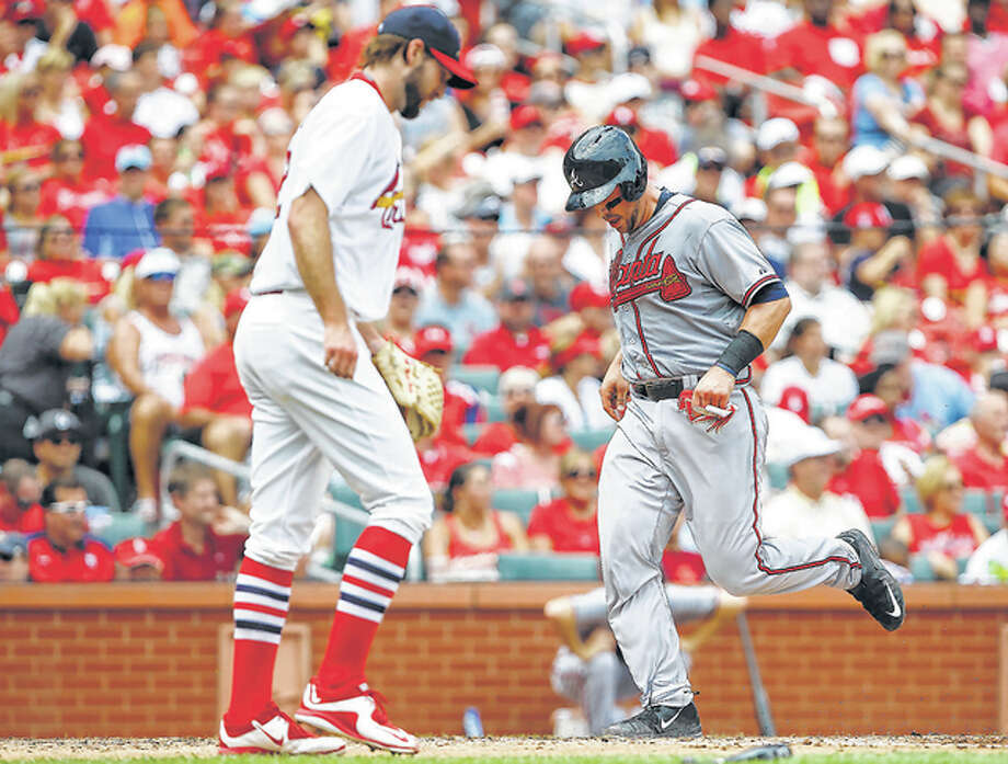 The Braves' Ryan Lavarnway, right, scores a run as Cardinals pitcher Michael Wacha, looks on Sunday at Busch Stadium. Photo: AP