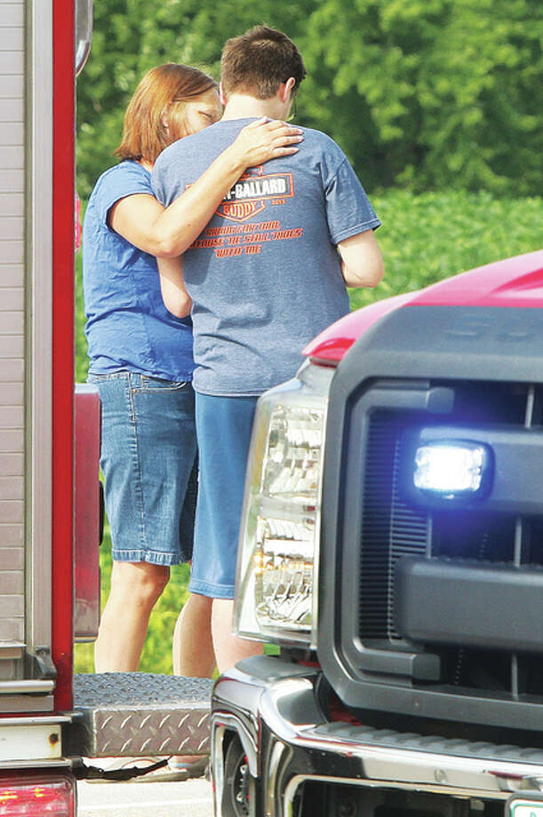 A woman tries to comfort the driver who struck and killed a pedestrian Monday on Illinois Route 140 east of Powder Mill Road in Alton. The driver was composed but distraught after the crash.