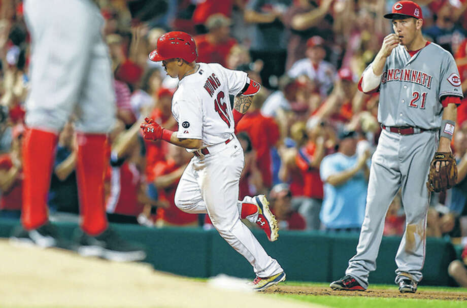 The Cardinals' Kolten Wong rounds the bases after hitting a grand slam as Reds third baseman Todd Frazier, right, looks on during in fourth inning Monday night at Busch Stadium. Photo: Scott Kane | AP