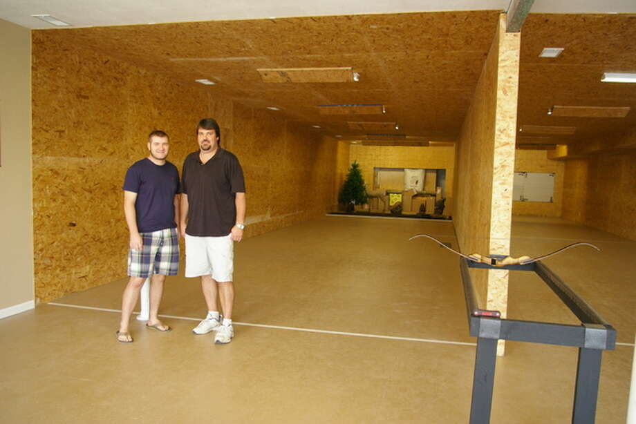 Brendan Manley, left, and Steve Russell, co-owners of recently opened 'Just Shoot' in East Alton, pose in their new indoor archery range.