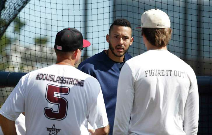 Houston Astros shortstop Carlos Correa (1) chats with Douglas Stoneman High School's baseball head coach Todd  Fitz-Gerald, left, and his son, Hunter Fitz-Gerald, right, watch the Astros batting practice during spring training at The Fitteam Ballpark of the Palm Beaches, Friday, Feb. 23, 2018, in West Palm Beach.