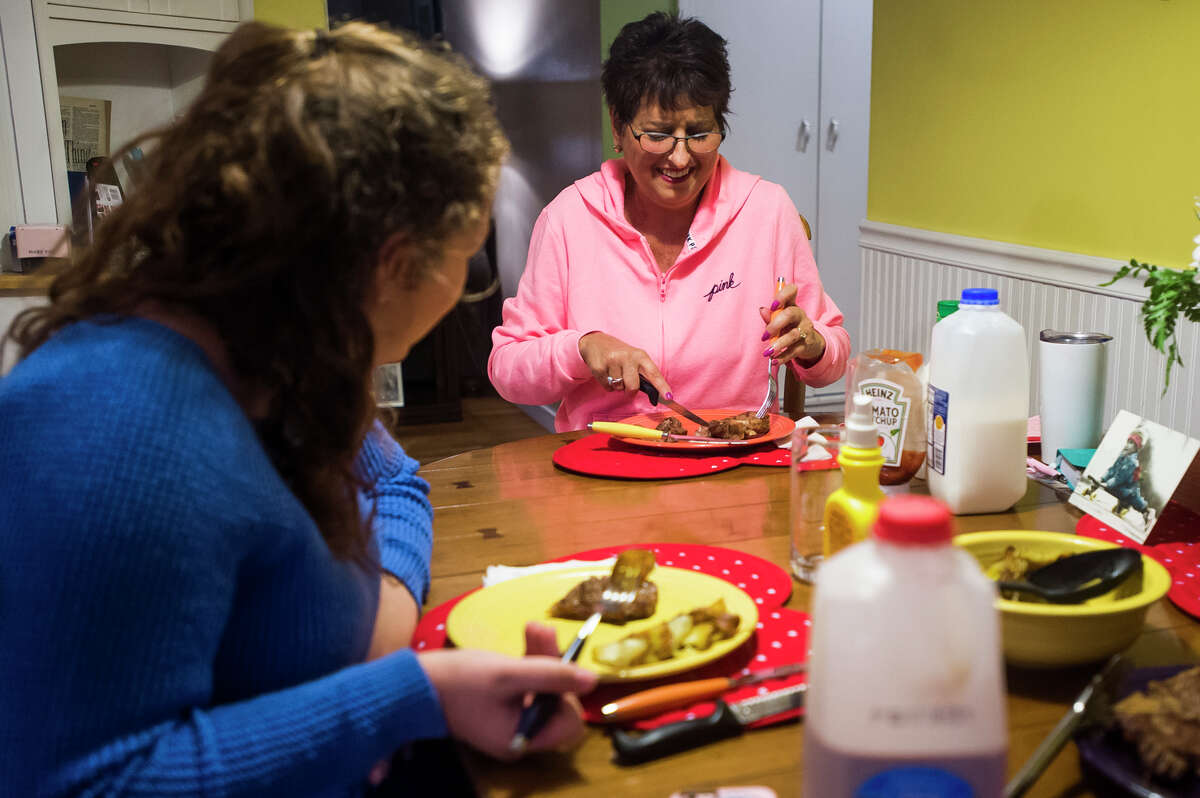 Angela Wojda enjoys dinner with her daughter Miranda, left, and husband Gus (not pictured) at their home on Tuesday, Feb. 20, 2018. (Katy Kildee/kkildee@mdn.net)