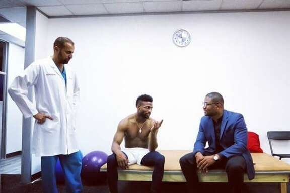 Denver Broncos wide receiver Emmanuel Sanders talks with Dr. Azim Karim and Edikan Adiakpan at Greater Texan Health facility in Houston after a therapy session for his ankle injury.