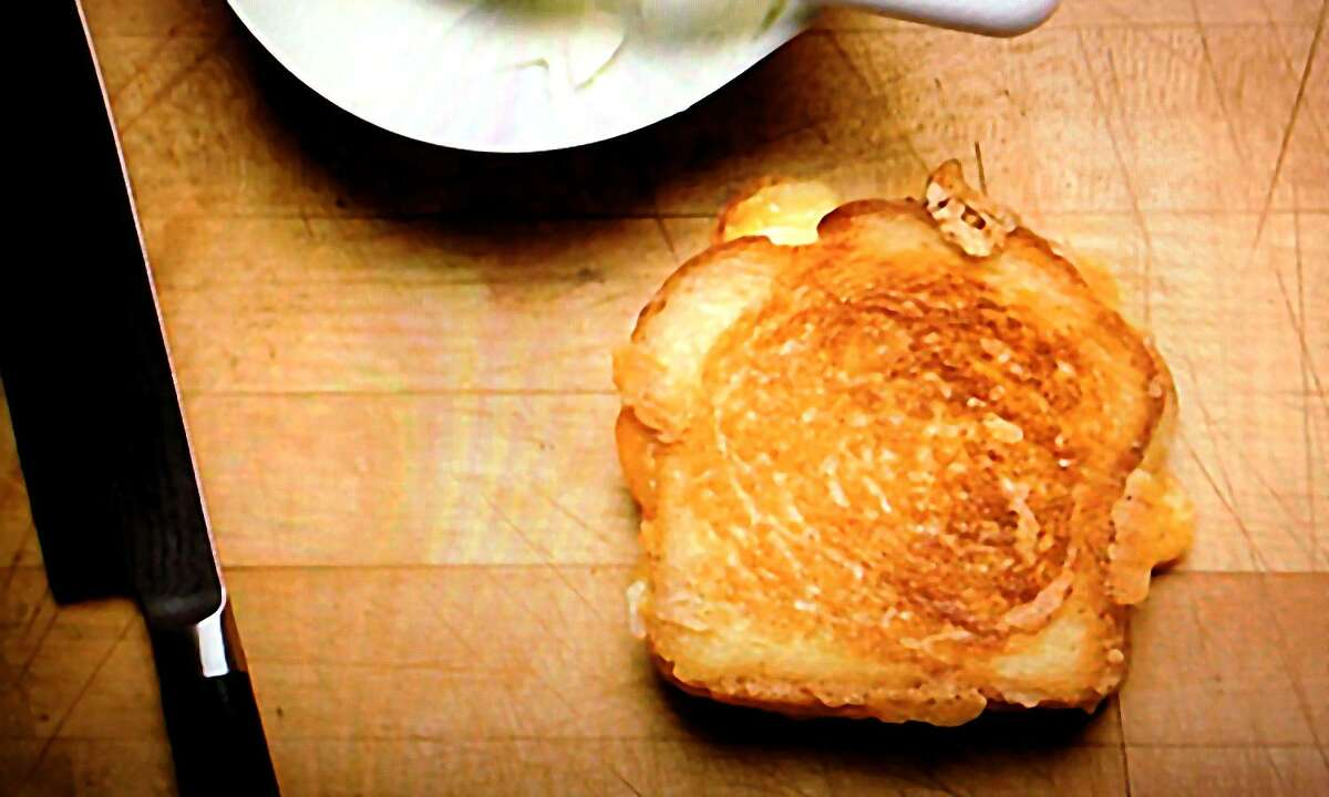 """A scene from the film """"Chef,"""" featuring a grilled cheese sandwich made by Jon Favreau's chef character for his son with Gruyère, Parmesan and cheddar cheeses."""