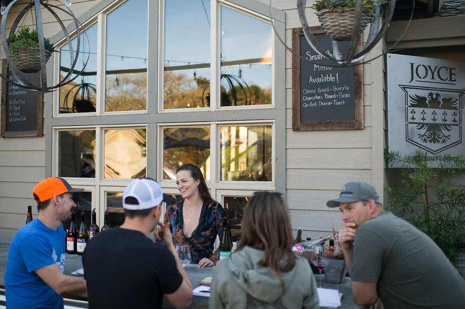 Wine educator Michaela Caul (center) pours for customers at Joyce Vineyards' newly built outside bar at its tasting room in Carmel Valley. Photo: Nic Coury, Special To The Chronicle