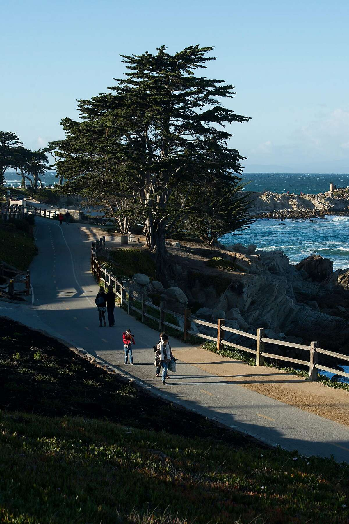 People walk along the Monterey Bay Coastal Recreation Trail near Lovers Point in Pacific Grove, Calif., which is one of Susan Love's favorite places to run on the Monterey Peninsula.