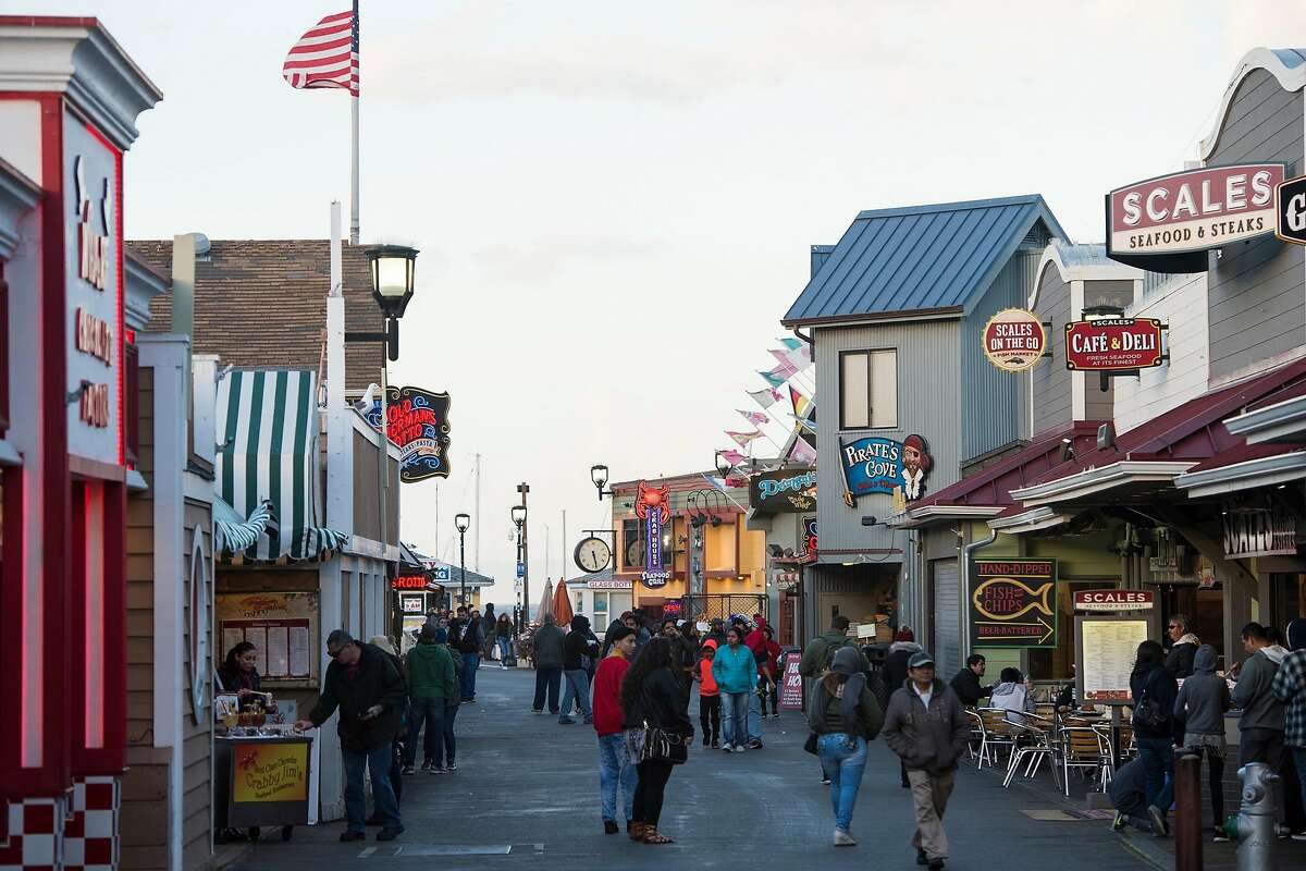 People walk along Old Fisherman's Wharf in Monterey, Calif. in Feb. 2018. Susan Love enjoys taking visitors on the Wharf to taste clam chowder.