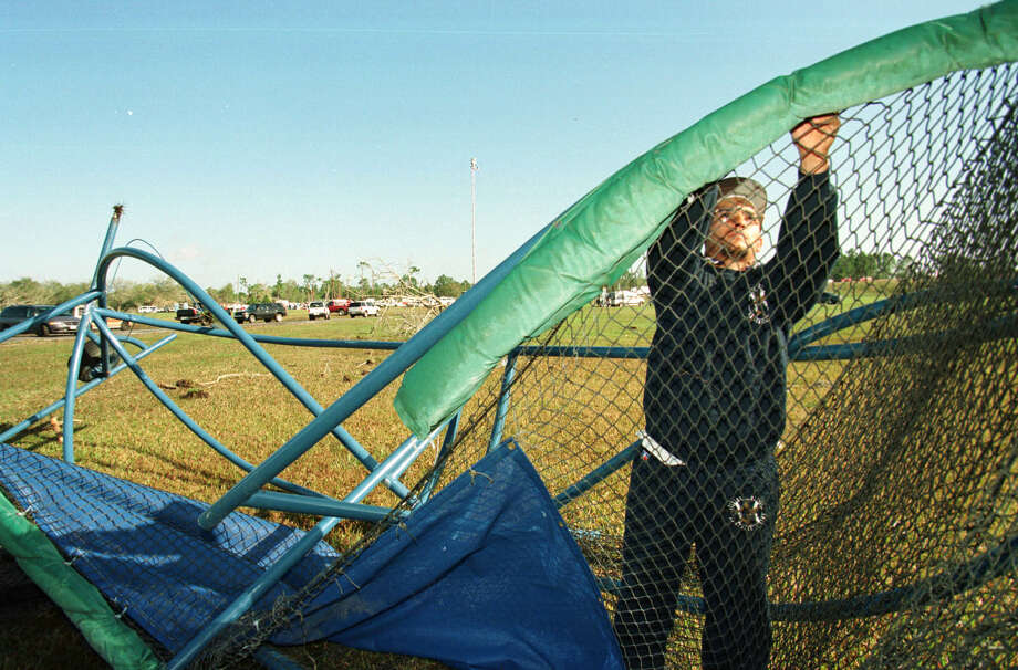 Anthony Soto, a groundskeeper at the Osceola Sports Complex, where the Astros train, dissembles the team's mangled battling cage Monday. In the distance is the Ponderosa RV Park, where eight people died. No team members suffered injuries from the tornado. Photo: Karen Warren, Houston Chronicle / Houston Chronicle