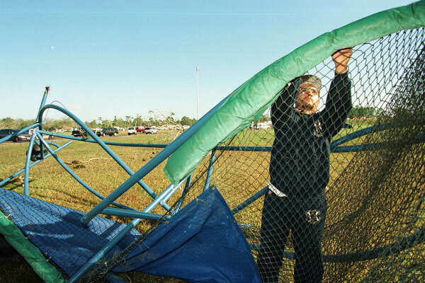 Anthony Soto, a groundskeeper at the Astros Complex, works to disassemble the Astros'  batting cage...in the background is the Ponderosa RV park...Photo/Karen Warren   HOUCHRON CAPTION (02/24/1998): Anthony soto, a groundskeeper at the Osceola Sports Complex, where the Astros train, dissembles the team's mangled battling cage Monday. In the distance is the Ponderosa RV Park, where eight people died. No team members suffered injuries from the tornado.