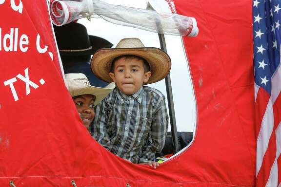 Jerry Henry Jr., 8, (left) and David Melchor, 4, enjoy the view from a covered wagon as the Northeastern Trail Riders made a stop at B.C. Elmore Middle School, 8200 Tate St., Friday, Feb. 23, 2018, in Houston.