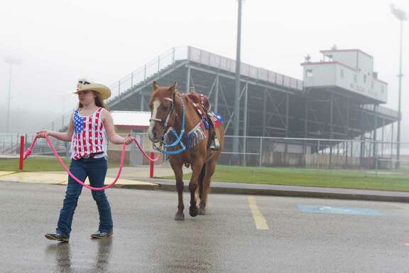 Second-grader Jadyn Thibodeaux prepares her horse 'Rusty' to ride to school alongside her mother, April Butler, as part of Piney Woods Elementary School's Go Texan Day, Friday, Feb. 23, 2018, in Splendora.